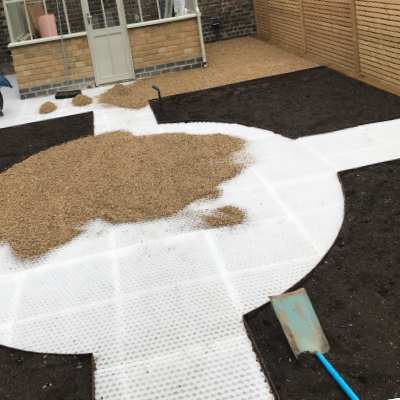 Pouring gravel on to garden landscape path